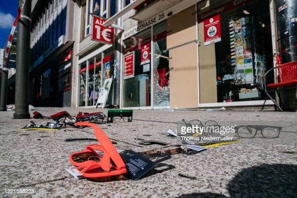 Glasses are seen on the floor as a display window of a shop stands smashed following violent clashes between rioters and police that also led to...