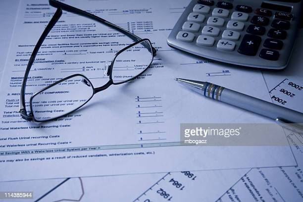 Glasses, calculator and pen on Financial cost documents