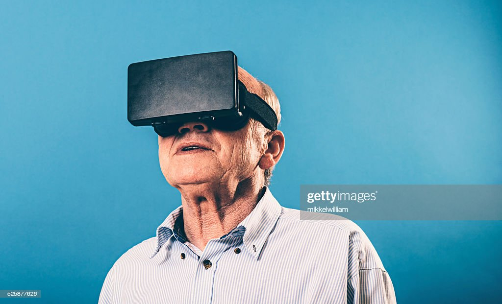 VR glasses gives senior man immersive experience : Stock Photo