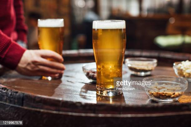glasses of beer and peanuts on a wooden table at a pub, a close up - snack stock pictures, royalty-free photos & images