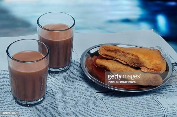 Glasses of chai and bread pakoras on newspaper