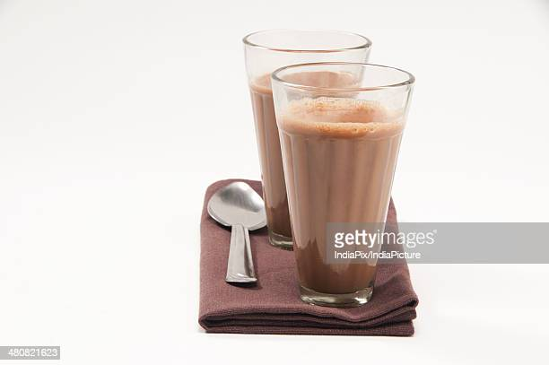 Glasses of chai and steel spoon kept on table napkin isolated over white background