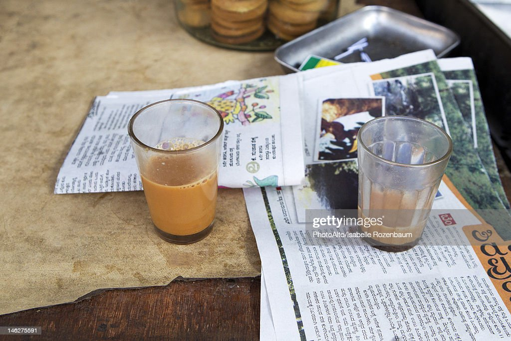 Glasses of chai tea and newspaper on table : Stock Photo