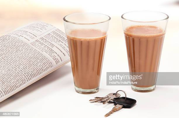 Glasses of chai with car keys and newspaper