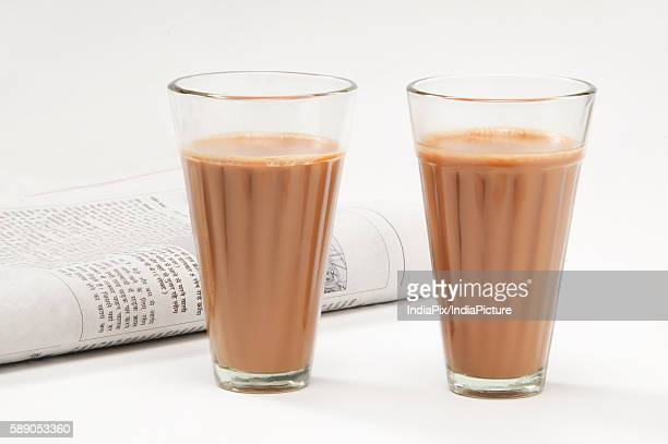 glasses of chai with newspaper isolated on white background - chai stock photos and pictures