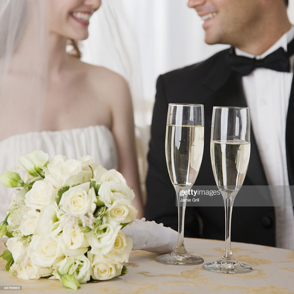 Glasses of champagne in front of bride and groom : Stock Photo