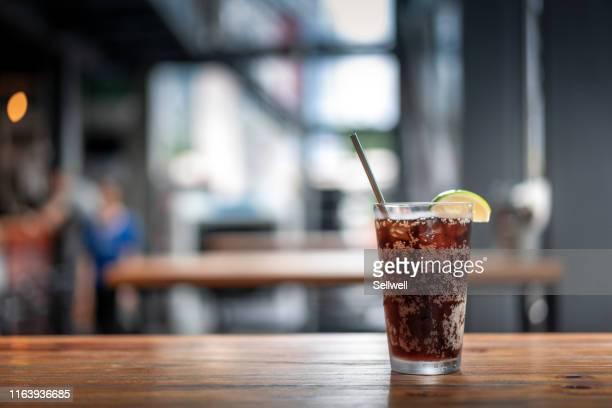 glasses of cola on the table - koude dranken stockfoto's en -beelden