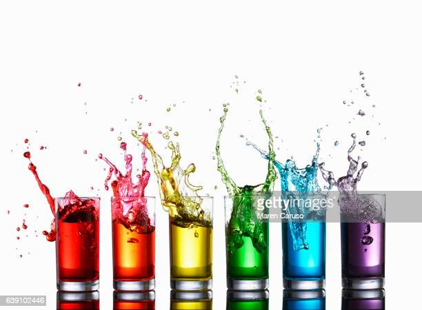 Glasses of colorful liquid splashing