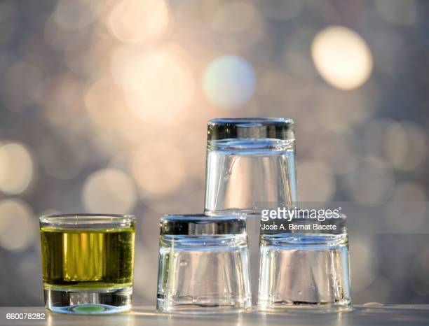 glasses of crystal of chupito one full and another emptiness  , illuminated by the light of the sun - dos objetos stock pictures, royalty-free photos & images