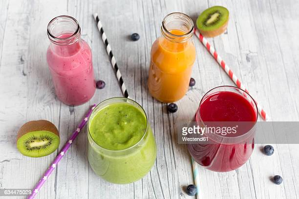 Glasses of four different smoothies and fruits on wood