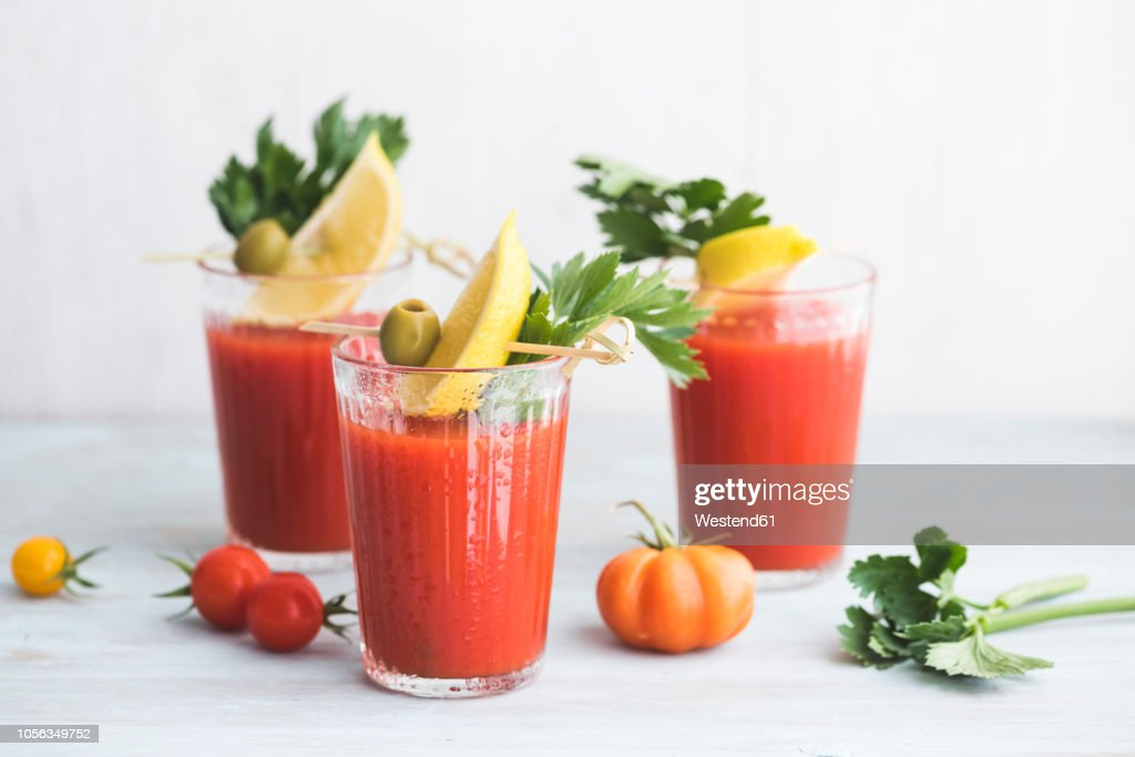 Glasses of fresh spicy tomato juice with cellery garnished with lemon slice, green olive and parsley : Stock Photo