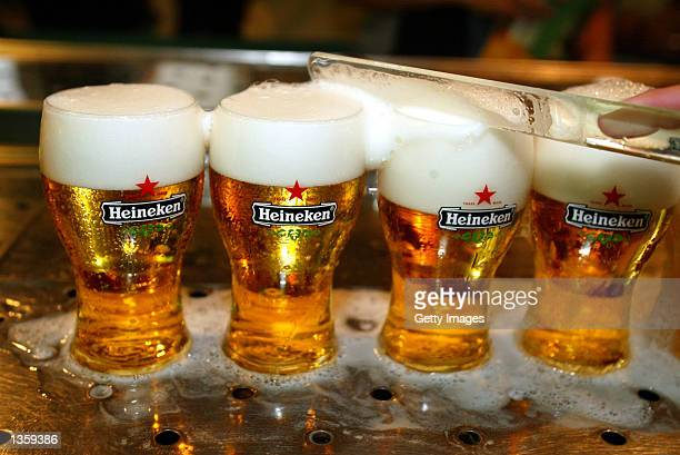 Glasses of Heineken beer with their brand's logo are prepared for consumption in a bar August 29 2002 in Amsterdam Netherlands The European...