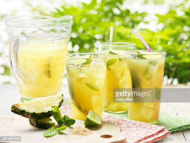 Glasses of home made golden rum punch with lime, pineapple, mint and ice