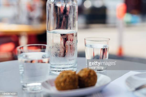 glasses of ice sparkling water and croquettes on dining table in spanish restaurant - mediterranean culture stock pictures, royalty-free photos & images