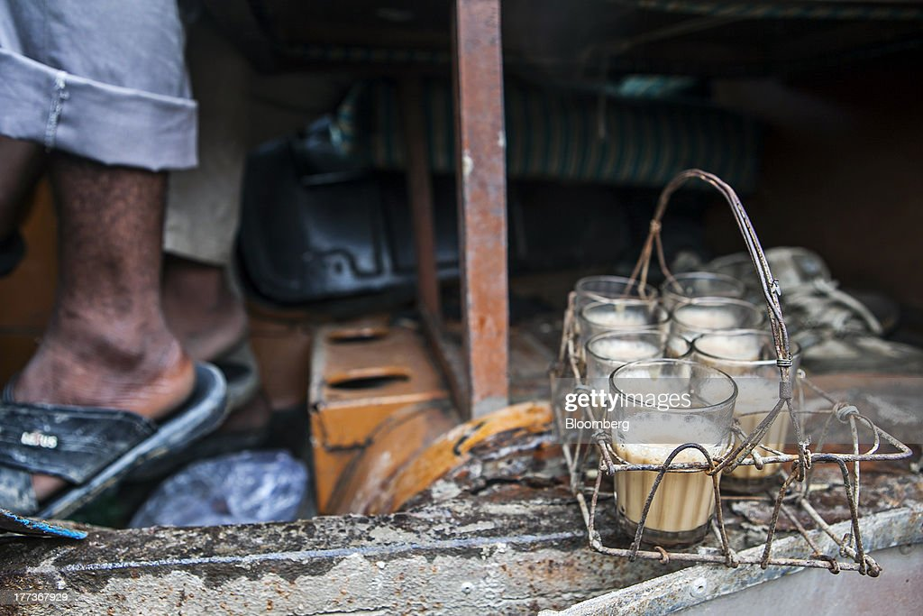 Glasses of Indian spiced chai tea sit at the feet of men resting in the cabin of a truck at the Sanjay Gandhi Transport Naga depot in New Delhi, India, on Thursday, Aug. 22, 2013. Indias rupee plunged 4.4 percent to a record this week in its worst performance since 1993 on signs the U.S. is getting closer to reducing stimulus that fueled demand for emerging-market assets. Photographer: Prashanth Vishwanathan/Bloomberg via Getty Images
