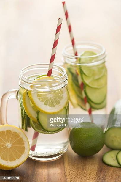 Glasses of infused water with lime, lemon, cucumber and ice cubes
