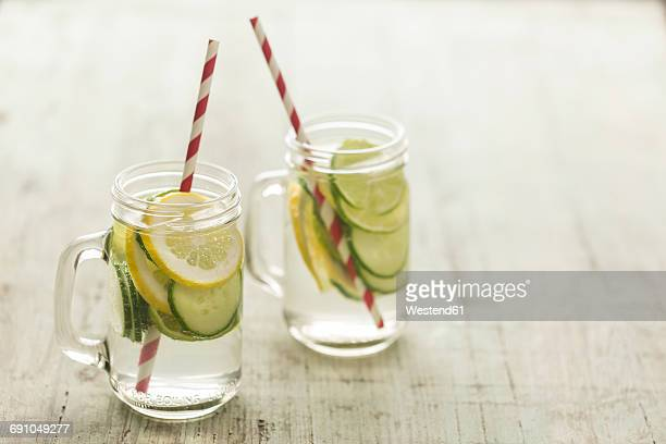 glasses of infused water with lime, lemon, cucumber and ice cubes - infused water stock pictures, royalty-free photos & images
