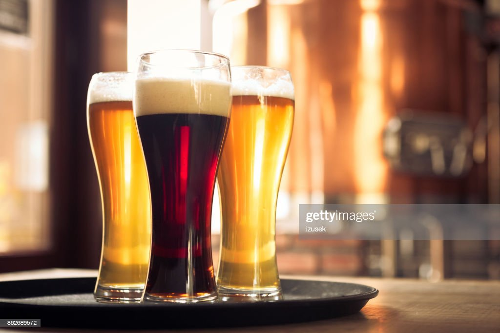 Glasses of lager and ale beer in front of copper vat : Stock Photo