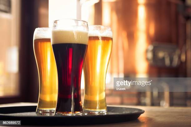 glasses of lager and ale beer in front of copper vat - ale stock pictures, royalty-free photos & images
