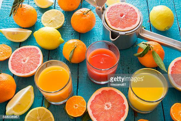 Glasses of orange juice, grapefruit juice and multivitamine juice, juice squeezer and fruits on wood