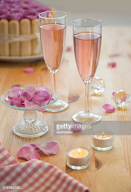 2 glasses of pink sparkling wine on wedding reception table top.