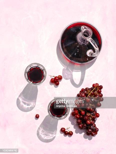 glasses of red wine, decanter and grape on pink background, top view - wine harvest stock pictures, royalty-free photos & images