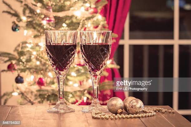 Glasses of red wine on table with decorated Christmas tree in background