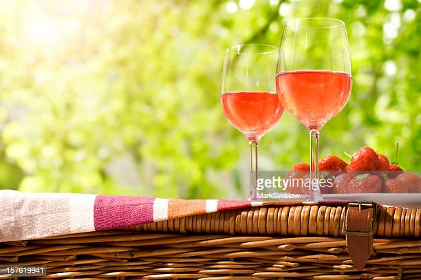 Glasses of rose wine and a plate of strawberries on a picnic
