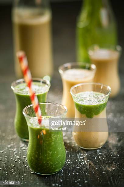 Glasses of spinach smoothie and mango smoothie with desiccated coconut on wooden table