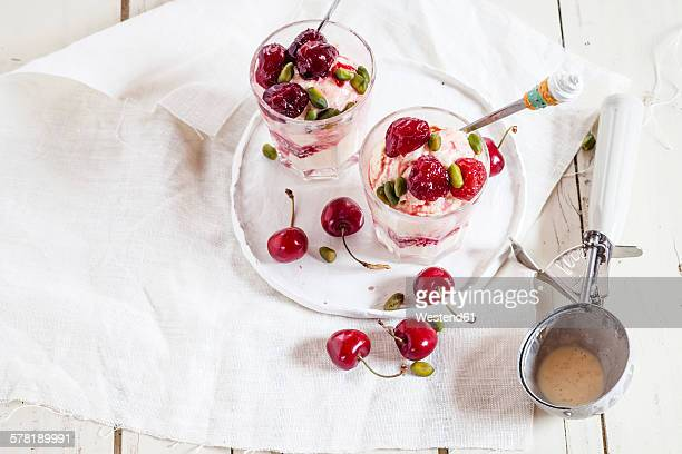 Glasses of vanilla icecream with amarena cherries and pistachios