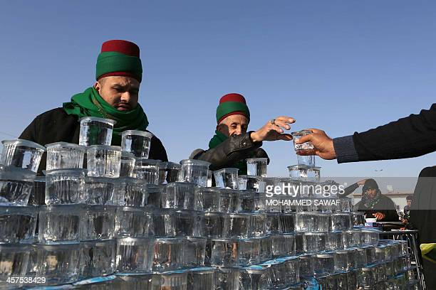 Glasses of water are given out to Iraqi Shiite Muslim pilgrims walking along the main highway from Najaf to the central shrine city of Karbala on...