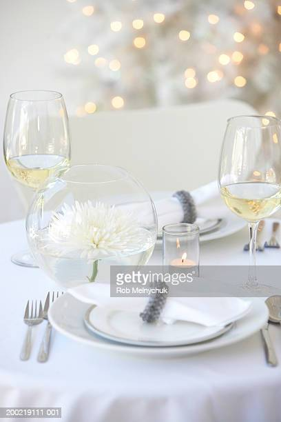 Glasses of white wine and centerpiece beside place setting on table