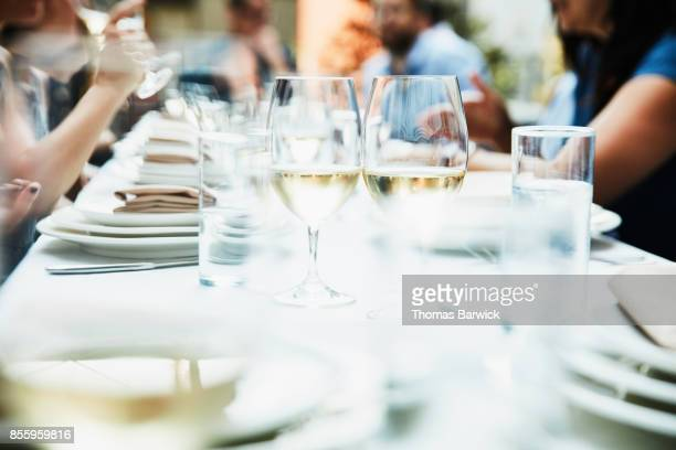 glasses of white wine on table during celebration dinner - 背景に人 ストックフォトと画像