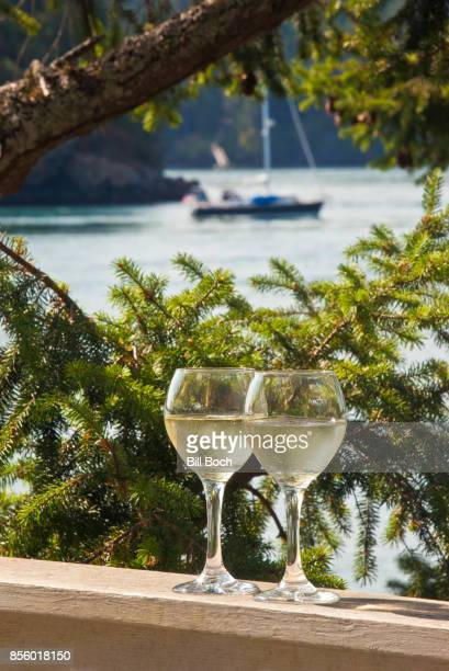 2 glasses of wine outside on a deck with a sailboat in the background on Orcas Island, WA