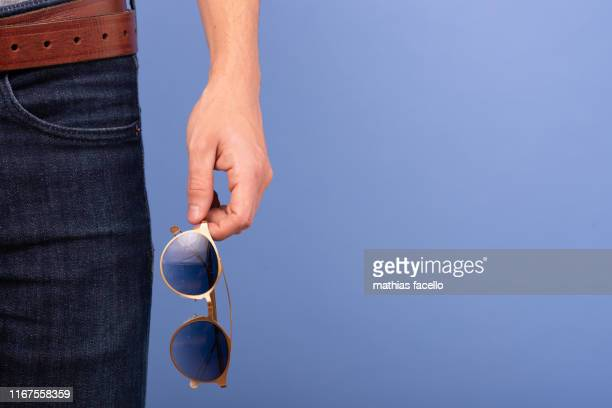 glasses on a man denim pocket with a grey shirt on a blue background - hands in her pants stock pictures, royalty-free photos & images