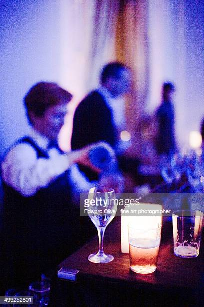 Glasses on bar and cocktail waiters in nightclub