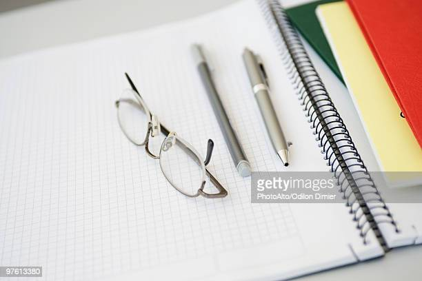 Glasses, pens on open notebook