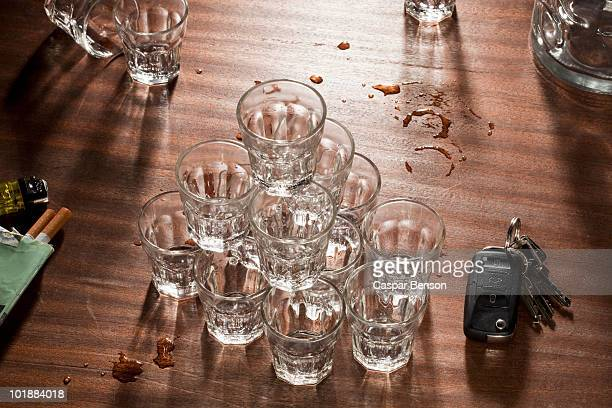 glasses stacked on top of each other on a messy table - 宴の後 ストックフォトと画像