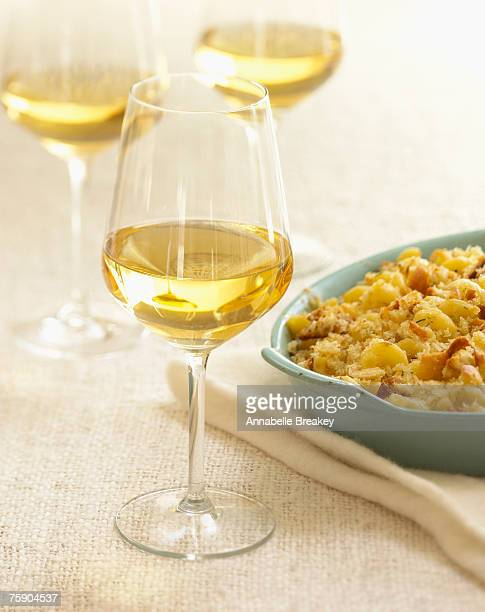 Glasses with white wine and serving dish of pasta, close-up