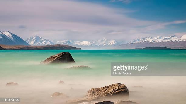 glassy waters of lake tekapo - lago tekapo fotografías e imágenes de stock