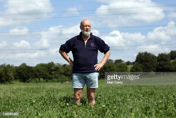 Glastonbury Festival founder Michael Eavis stands in a field of uncut grass in front of the skeleton of the main Pyramid Stage at the Glastonbury...