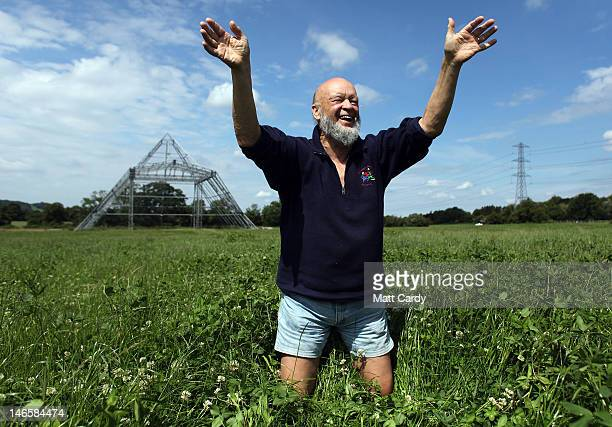 Glastonbury Festival founder Michael Eavis waves as he stands in a field of uncut grass in front of the skeleton of the main Pyramid Stage at the...