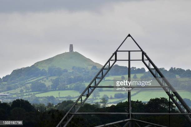 Glastonbury Tor rises behind the skeleton of the famous Pyramid stage at Worthy Pastures on the site of the Glastonbury Festival held at Worthy Farm,...