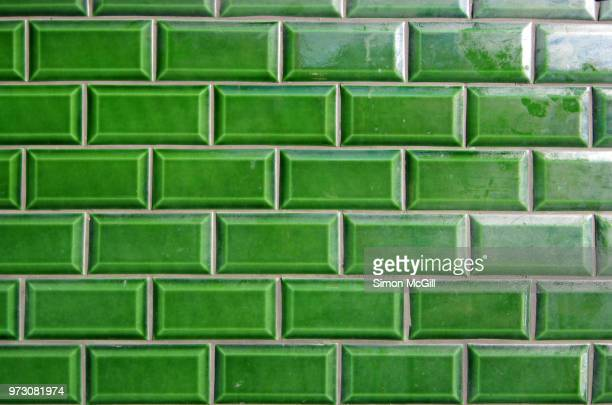 glazed green rectangular tiles with bevelled edges on the exterior wall of a building - tile stock photos and pictures
