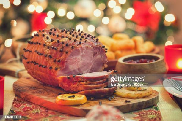glazed holiday ham in front of a christmas tree - glazed ham stock pictures, royalty-free photos & images