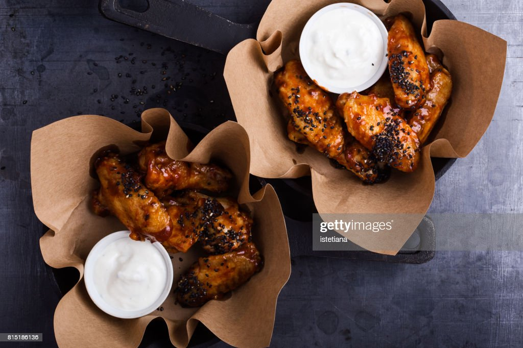 Glazed spicy chicken wings with sesame seeds served in cast iron skillets : Stock Photo