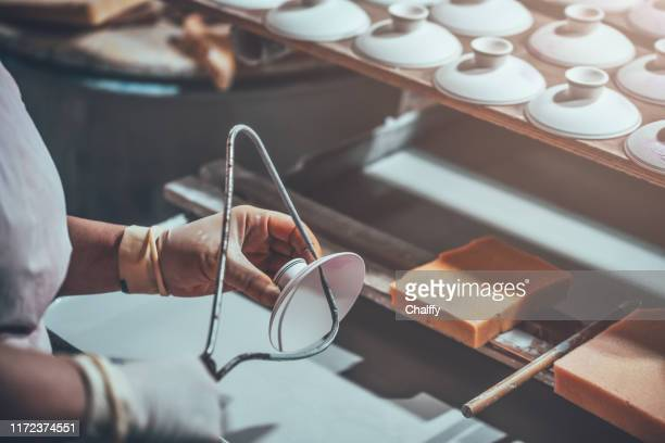 glazing a porcelain cup in a factory - porcelain stock pictures, royalty-free photos & images