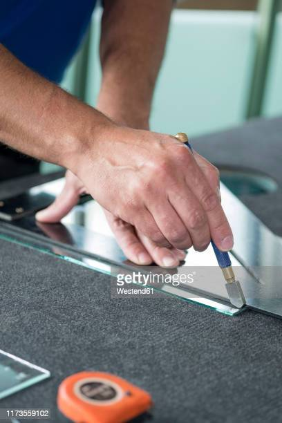 glazing, glazier during work, cutting glass with glass cutter - glass cutter stock photos and pictures