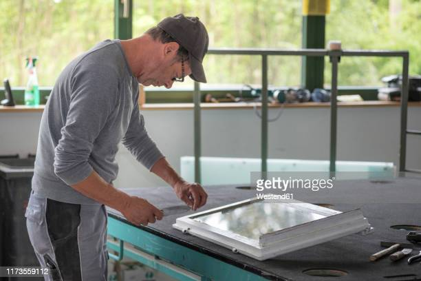 glazing, glazier during work with tool on window frame - glazed food stock pictures, royalty-free photos & images