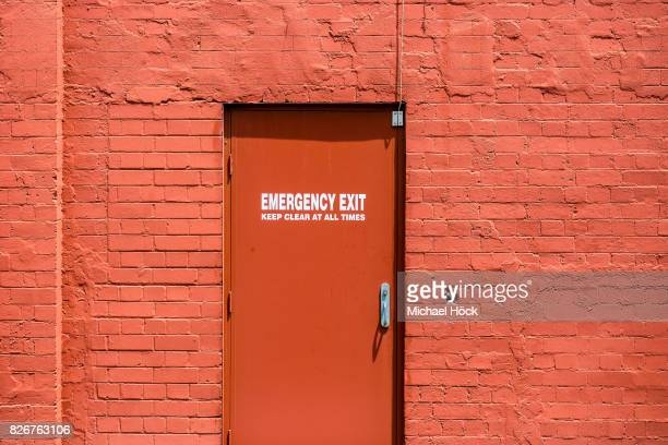 gleaming red wall with red emergency exit door - evacuation stock pictures, royalty-free photos & images